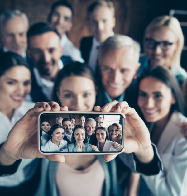 Close up blurry photo business people different age race free time excited team building hug embrace cuddle she her he him his telephone smart phone make take selfies formal wear jackets shirts.